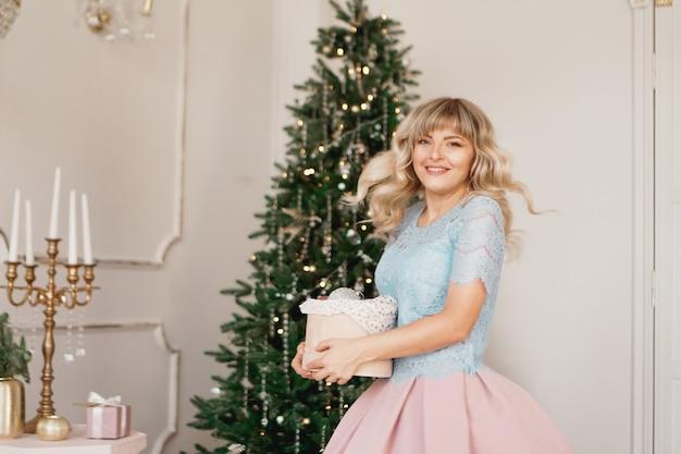 La giovane donna decora l'albero di natale con i giocattoli di natale interni classici in bianco e oro