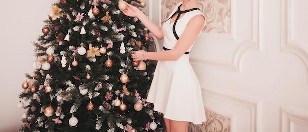 La giovane donna decora un albero di natale