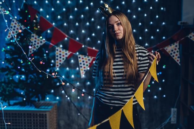 Una giovane donna decora la stanza bandiere, ghirlande che si preparano per la celebrazione del natale.