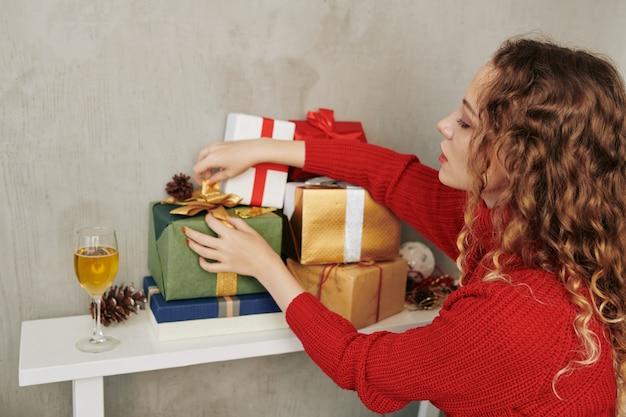 Giovane donna che decora i regali di natale