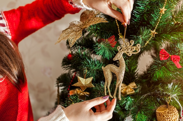 Giovane donna che decora l'albero di natale con i giocattoli a casa, indossando un maglione invernale.