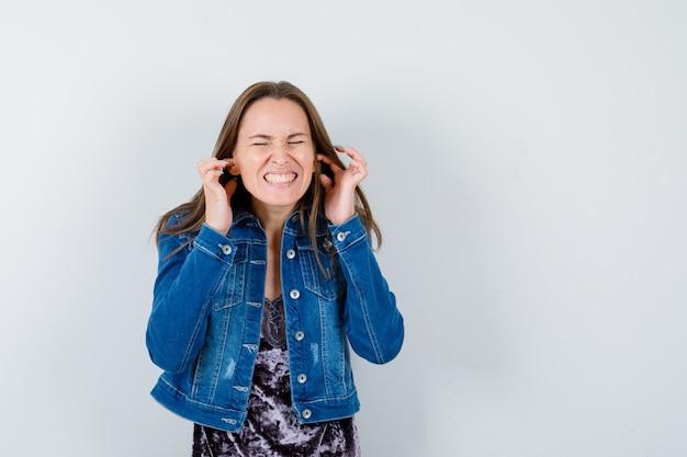 Giovane donna in giacca di jeans, vestito che tappa le orecchie con le dita, chiude gli occhi e sembra spaventata, vista frontale.