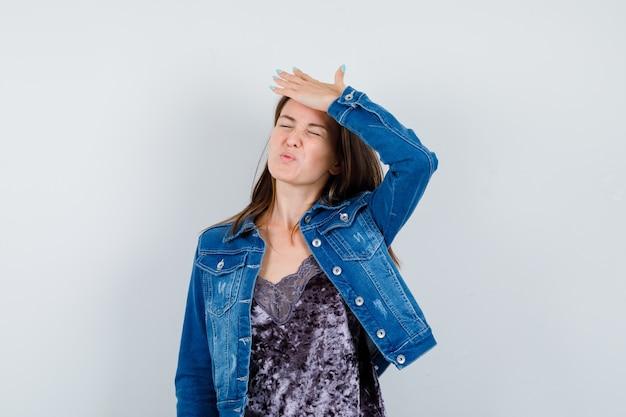 Giovane donna in giacca di jeans, vestito con la mano sulla testa e dall'aspetto pentito, vista frontale.