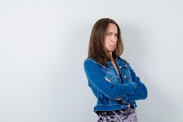 Giovane donna in giacca di jeans, vestito con le mani incrociate e guardando insoddisfatto, vista frontale.