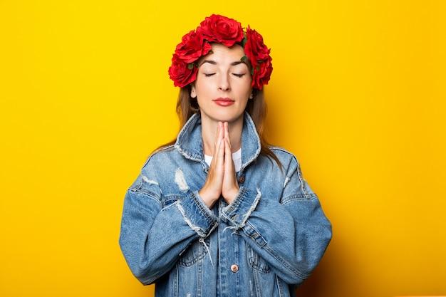 Giovane donna in una giacca di jeans e una ghirlanda di fiori rossi sulla testa incrociò le braccia in una posa yoga su un muro giallo.