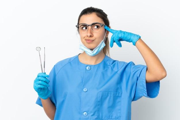 Strumenti di tenuta del dentista della giovane donna isolati avendo dubbi e pensando