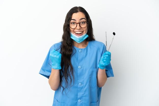 Dentista della giovane donna che tiene gli strumenti isolati su priorità bassa bianca che celebra una vittoria nella posizione del vincitore