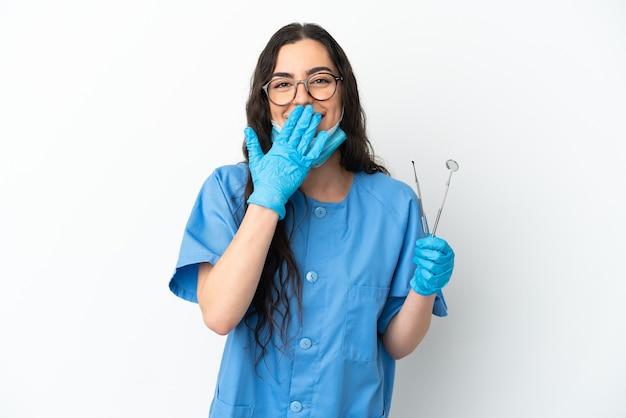 Dentista della giovane donna che tiene gli strumenti isolati su fondo bianco felice e sorridente che copre la bocca con la mano