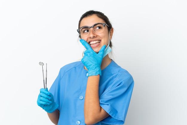 Strumenti della tenuta del dentista della giovane donna isolati su fondo bianco felice e sorridente