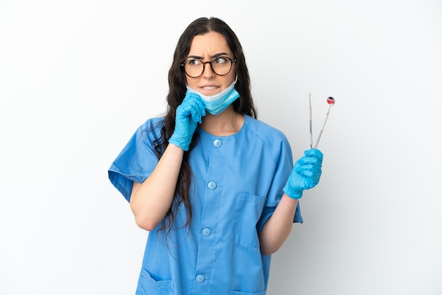 Strumenti della tenuta del dentista della giovane donna isolati su fondo bianco che ha dubbi e che pensa