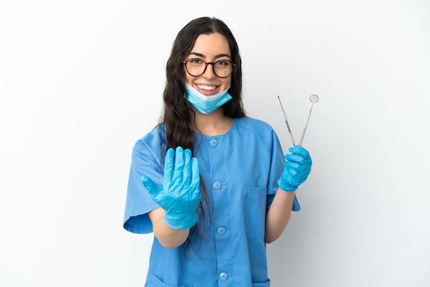 Dentista della giovane donna che tiene gli strumenti isolati su priorità bassa bianca che invita a venire con la mano. felice che tu sia venuto