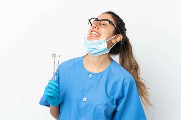 Strumenti della tenuta del dentista della giovane donna isolati su fondo bianco che ride