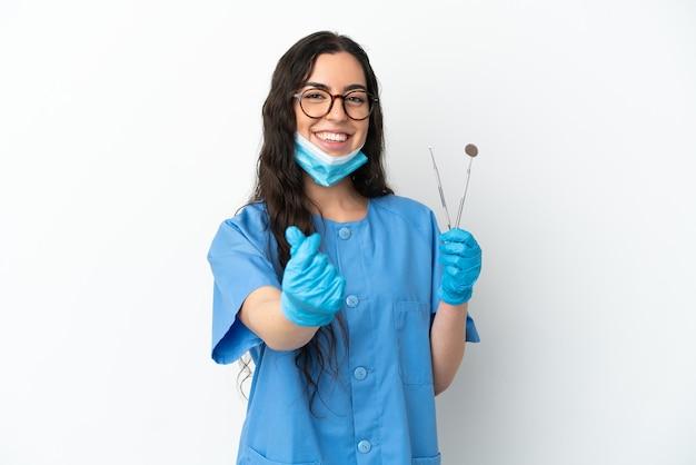 Strumenti della tenuta del dentista della giovane donna isolati su fondo bianco che fa i soldi gesture