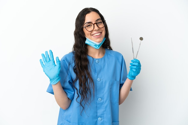 Dentista della giovane donna che tiene strumenti isolati su priorità bassa bianca che saluta con la mano con l'espressione felice