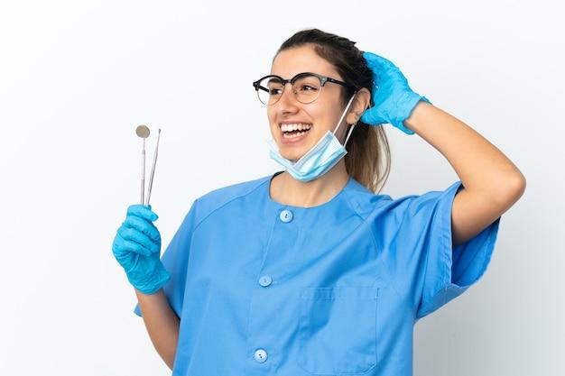 Strumenti della tenuta del dentista della giovane donna isolati su fondo bianco che sorride molto