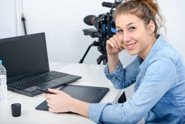 Designer di giovane donna che utilizza la tavoletta grafica per l'editing video