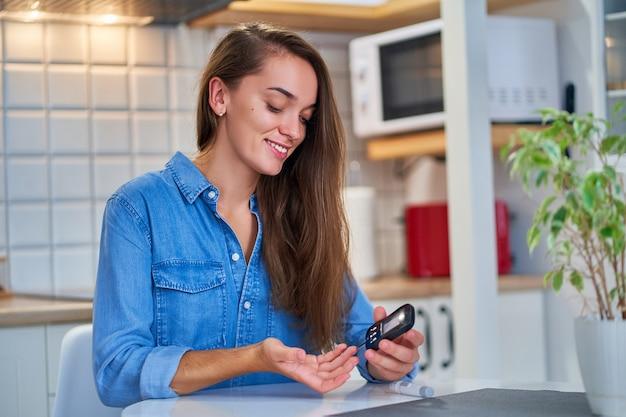 La giovane donna diabetica controlla e misura il livello di glucosio nel sangue utilizzando il glucometro. trattamento e controllo del diabete da zucchero, assistenza sanitaria