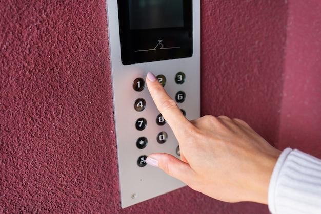 Una giovane donna compone il codice dell'appartamento sul pannello di un citofono elettronico. protezione e concetto di sicurezza.