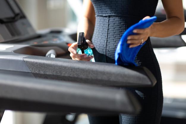 Giovane donna disinfezione pulizia attrezzature da palestra fitness con spruzzatore di alcol.