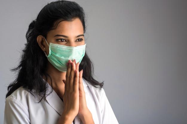 Medico della giovane donna che fa namaste a causa dello scoppio di covid-19. nuovo saluto per evitare la diffusione del coronavirus invece di salutare con un abbraccio o una stretta di mano.