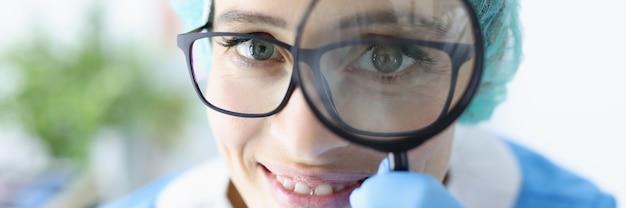 Il medico della giovane donna in vetri e uniforme tiene la lente d'ingrandimento vicino al suo ritratto degli occhi