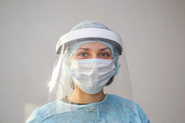 Giovane donna medico infermiere in maschera protettiva su sfondo bianco