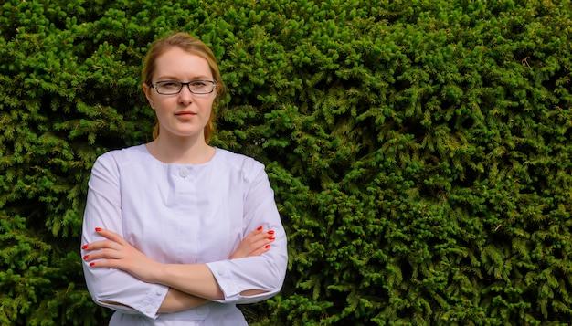 Medico della giovane donna, nutrizionista in camice e vetri su fogliame verde con lo spazio della copia. immagine per la pubblicità di sviluppi scientifici nel settore alimentare e medico.