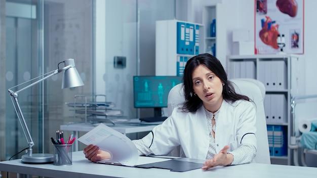 Medico di giovane donna che offre consulenza medica online dal moderno ufficio della clinica privata. medico che utilizza la tecnologia internet per consultare i pazienti durante la pandemia globale covid-19. telemedicina e sanità
