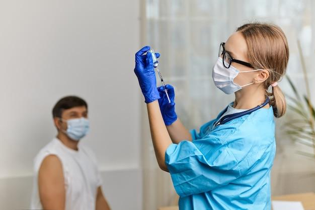 Giovane donna medico vaccina contro il coronavirus covid 19 a un giovane nell'ufficio di una clinica medica