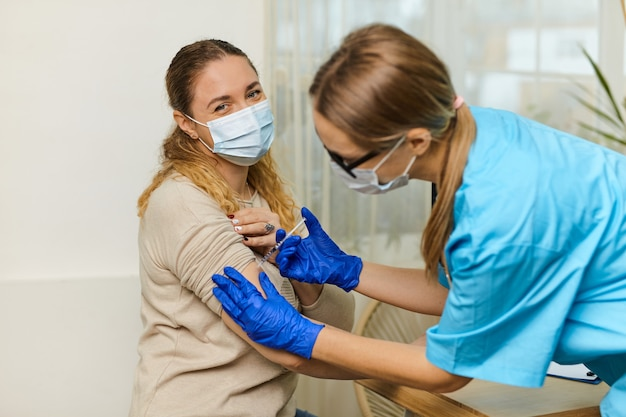 Giovane donna medico vaccina contro il coronavirus covid 19 a una giovane donna nell'ufficio di una clinica medica