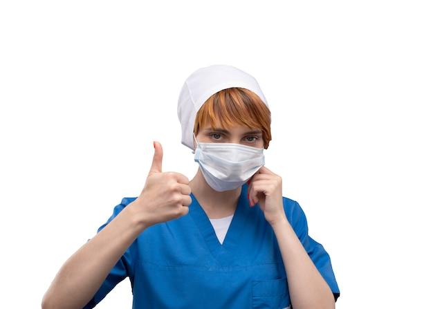 Il medico della giovane donna con una mascherina medica sul suo fronte mostra il pollice in su