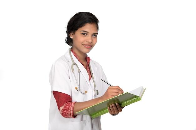 Il medico della giovane donna con lo stetoscopio sta scrivendo nel libro