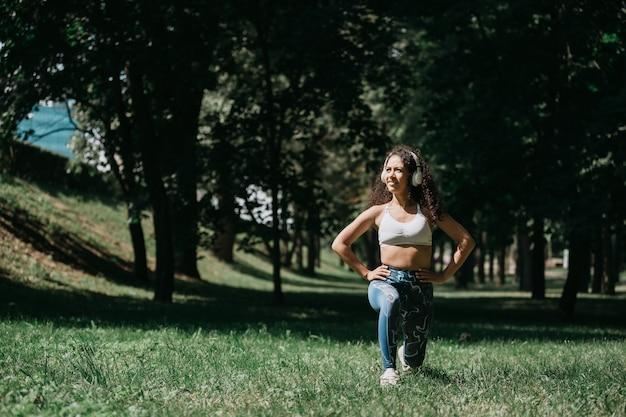 La giovane donna fa gli esercizi mattutini all'aperto foto con una copia s