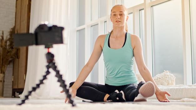 La giovane donna fa l'apprendimento a distanza in linea mentre blogga.
