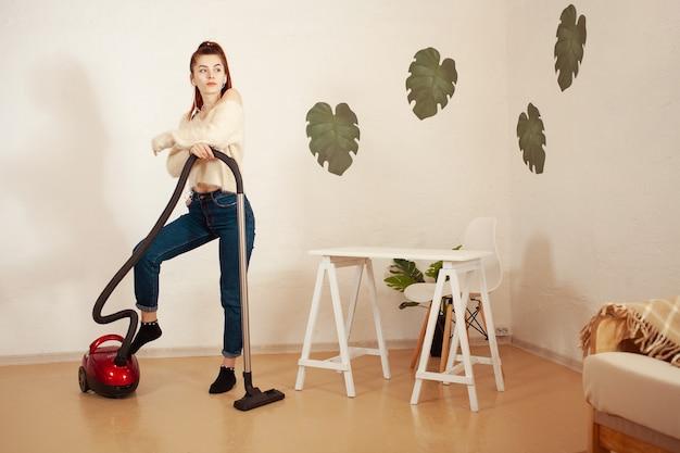 Giovane donna che fa le pulizie in casa una donna aspira il pavimento con un aspirapolvere