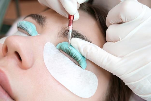 Giovane donna che fa la procedura di laminazione delle ciglia in un salone di bellezza, primo piano