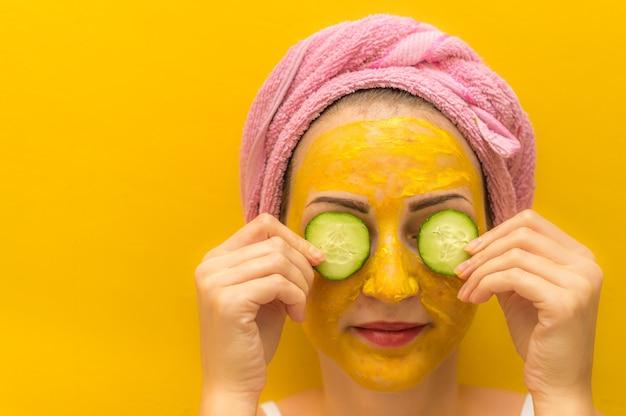 Giovane donna che fa la cura della pelle del viso a casa.