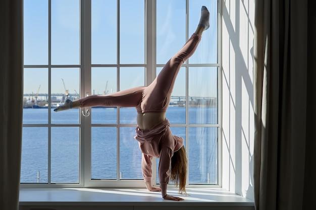 Giovane donna che fa la verticale sul davanzale della finestra del suo appartamento