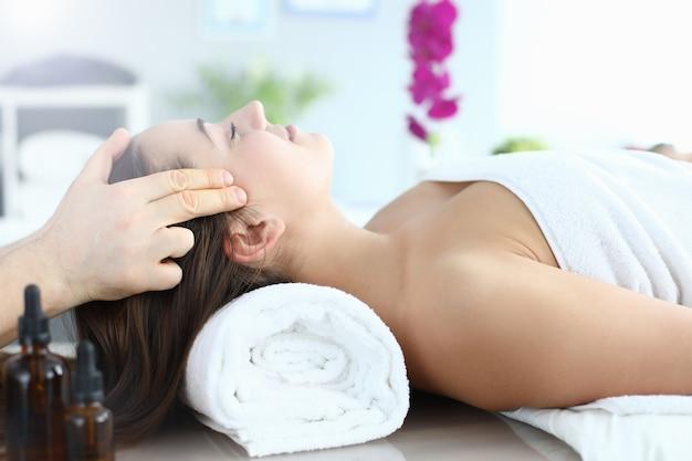 Giovane donna che fa massaggio alla testa nel centro termale