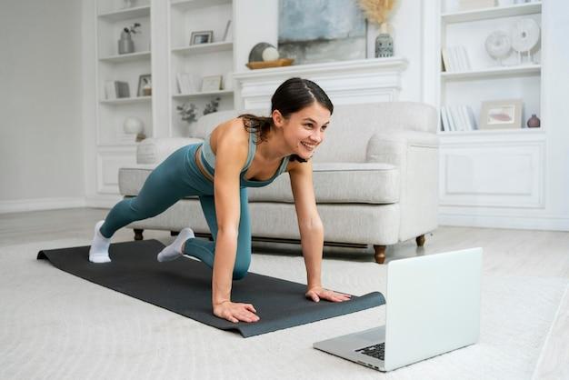 Giovane donna che fa il suo allenamento su un tappetino fitness