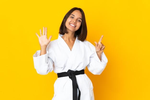Giovane donna che fa karate isolato su sfondo giallo contando sette con le dita