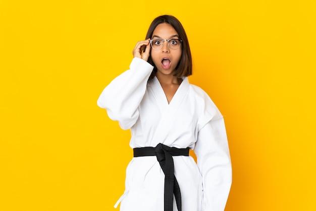 Giovane donna che fa karate isolato sulla parete gialla con gli occhiali e sorpreso