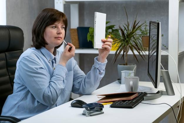 Giovane donna che fa trucco e si pavoneggia sul posto di lavoro. la ragazza dipinge le labbra al lavoro in ufficio. orario di lavoro