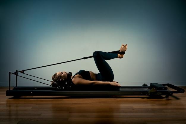 La giovane donna che fa i pilates si esercita con un letto del riformatore. bellissimo istruttore di fitness sottile