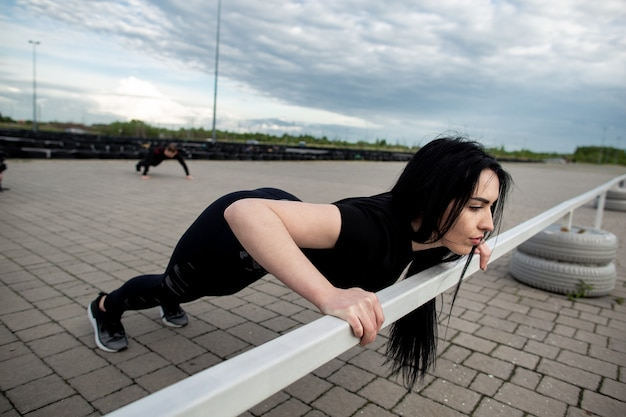 Giovane donna che fa push up sulla barra orizzontale all'esterno. donna che si allena vicino allo stadio. concetto di fitness, sport, esercizio e stile di vita.