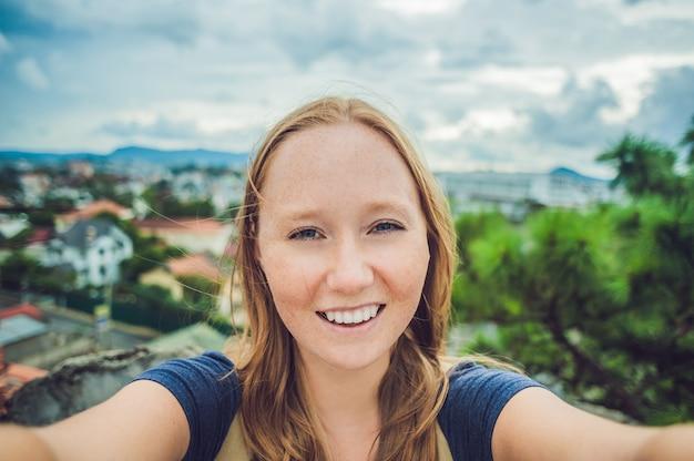 Giovane donna che fa selfie sullo sfondo della città di dalat