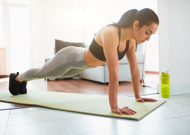 Giovane donna che fa allenamento di sport nella sala durante la quarantena. basamento calmo concentrato della ragazza nella posizione della plancia facendo uso delle mani. abbassa lo sguardo con concentrazione.