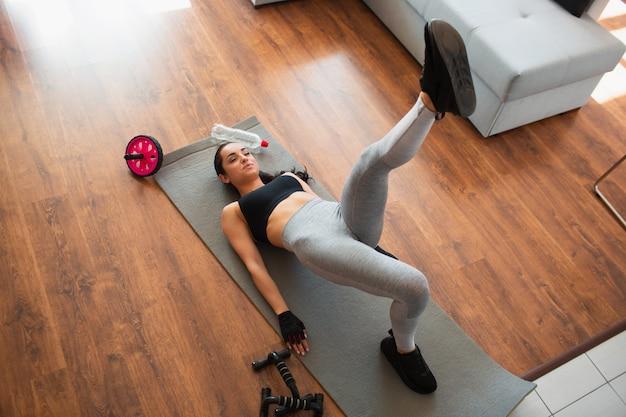 Giovane donna che fa allenamento di sport nella sala durante la quarantena. sdraiato sul tappetino e tieni la gamba sinistra in alto. esercizio di gambe. allenamento a casa senza attrezzatura.