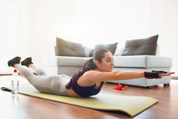 Giovane donna che fa allenamento di sport nella sala durante la quarantena. sdraiato sul tappetino e in avanti con le mani. esercizio a casa senza attrezzatura.