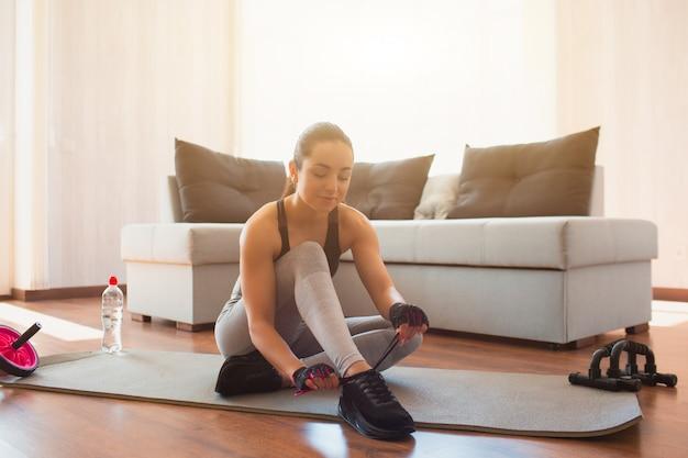 Giovane donna che fa allenamento di sport nella sala durante la quarantena. sedersi sul tappetino e stringere i lacci delle scarpe. prepararsi all'allenamento a casa.